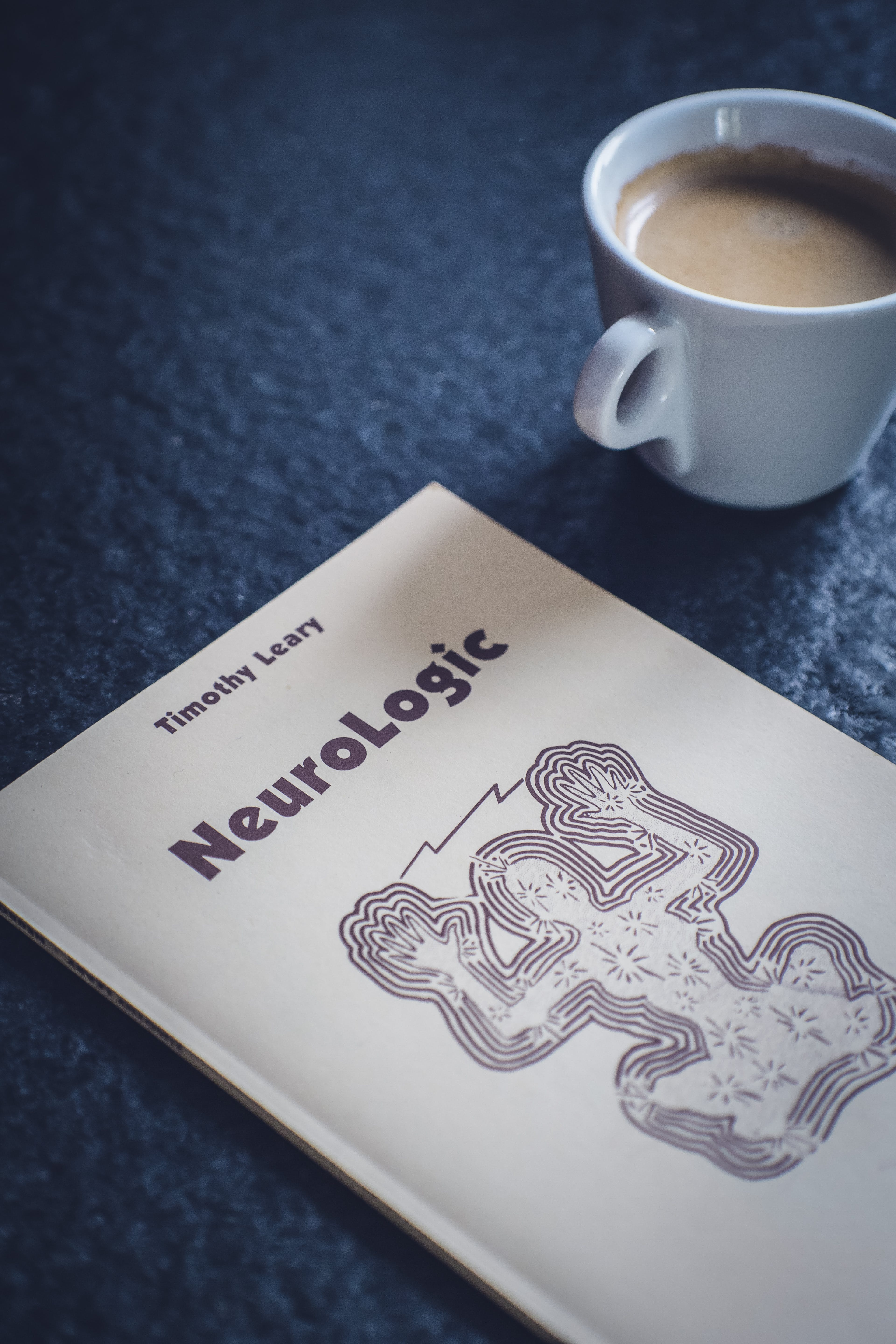Timothy Leary's Neurologic Book Near White Ceramic Cup