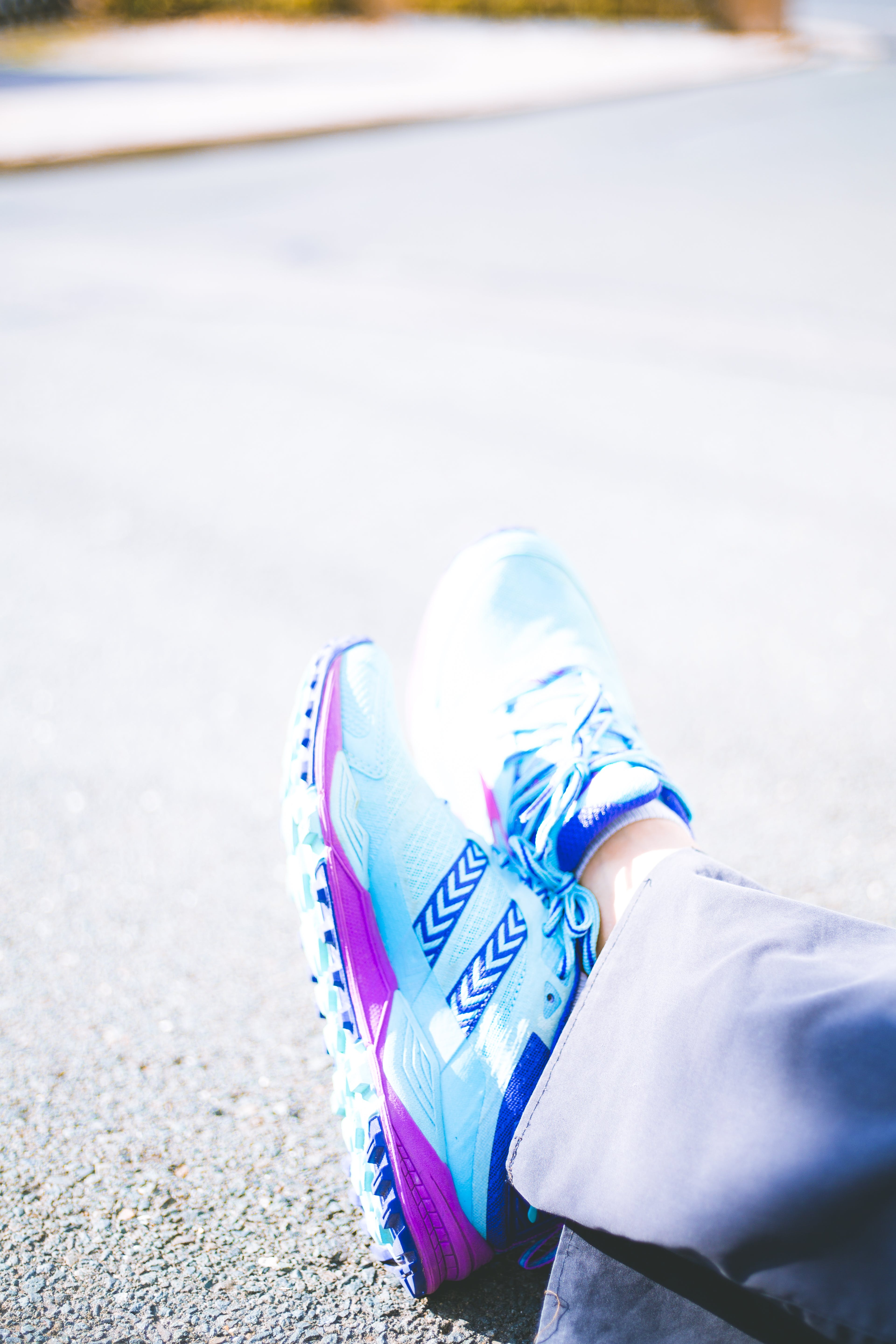 Person Wearing Pair of Blue-and-pink Running Shoes