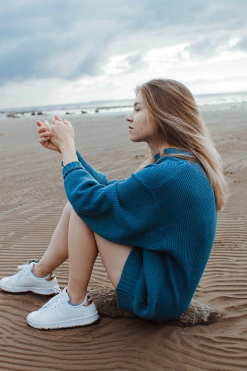 Woman in Blue Sweater Sitting on Beach Shore