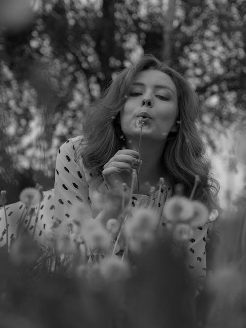 Grayscale Photo of Girl in Polka Dot Long Sleeve Shirt Blowing Dandelion Flower