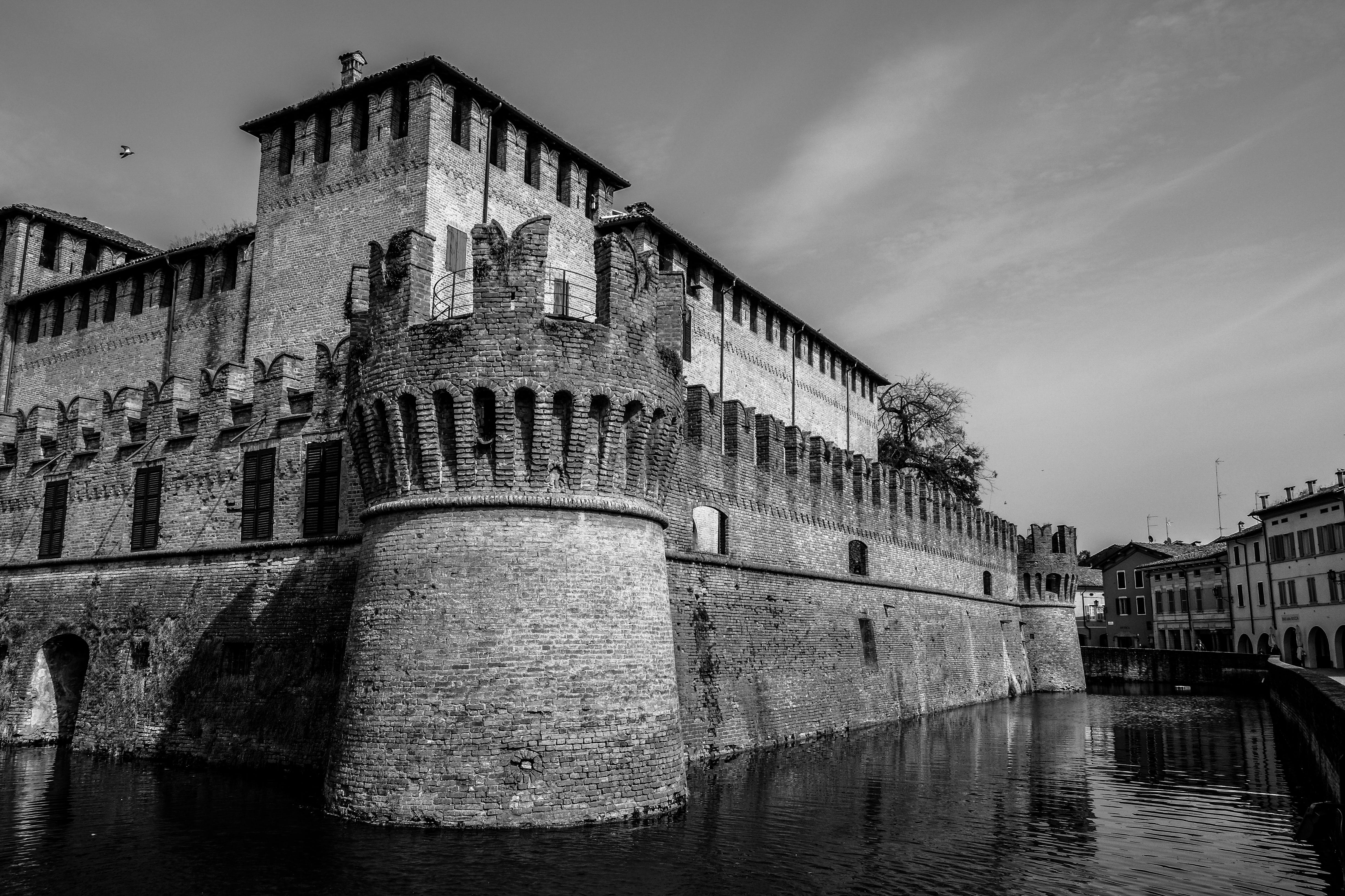 Grayscale Photography of Castle Near Body of Water