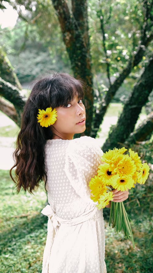 Girl in White Dress Holding Yellow Flowers