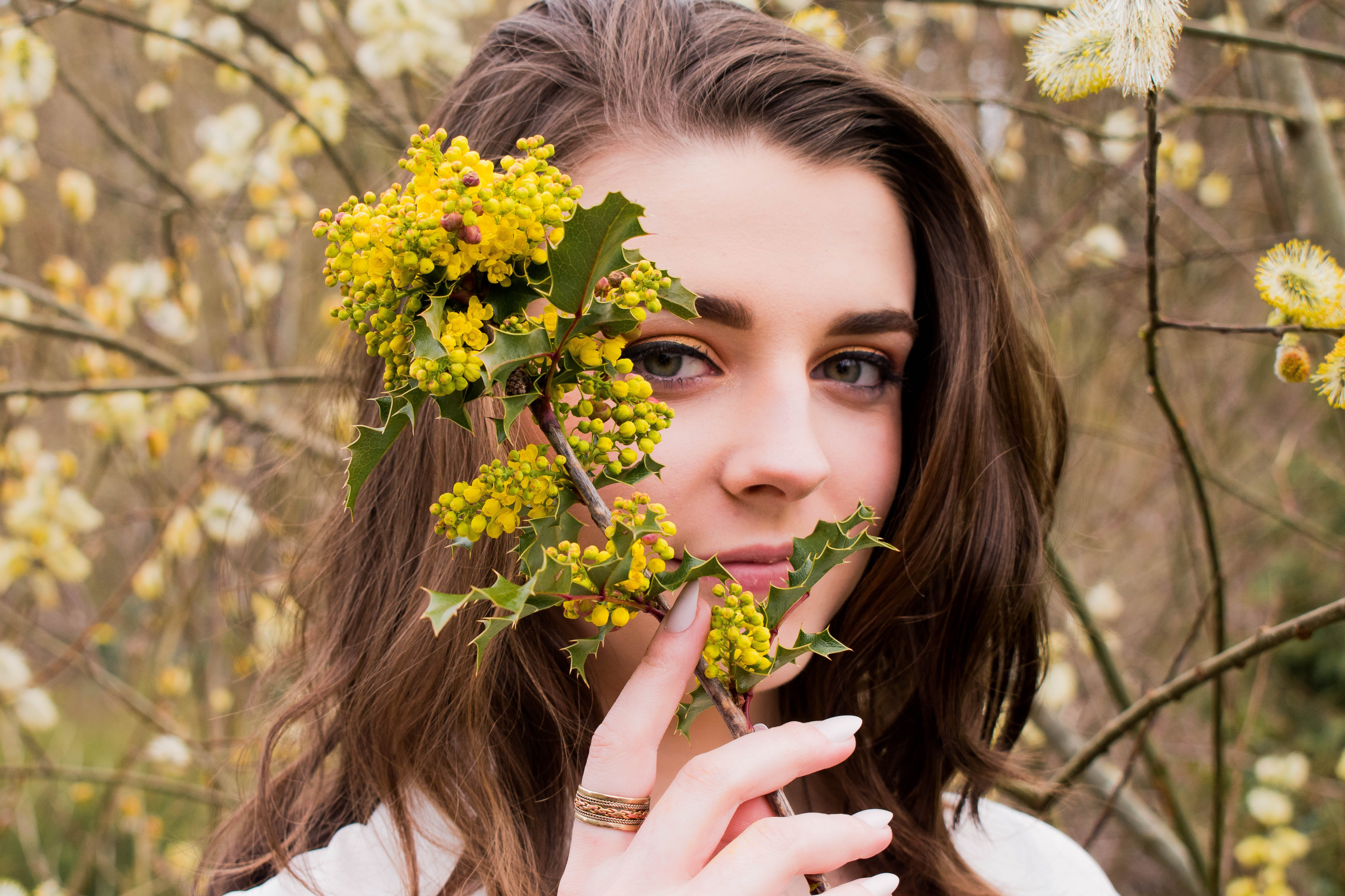 Woman Taking Photo With Holding Yellow Flower Buds at Daytime