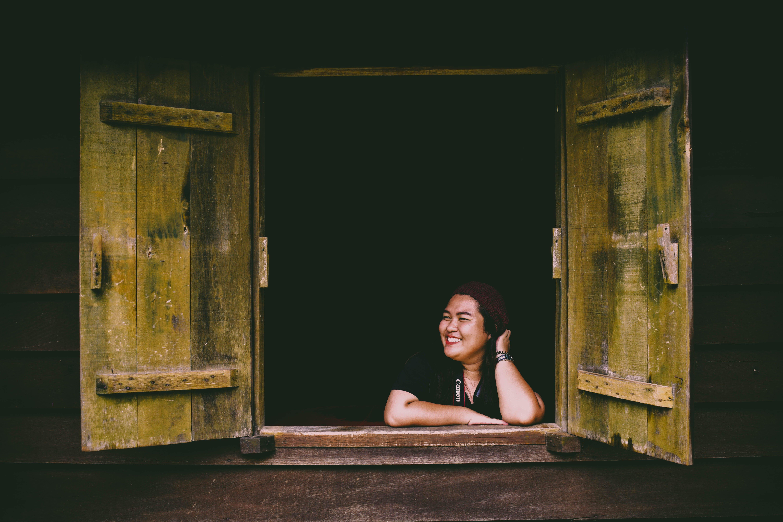 Woman in Black Top Sitting in Front of Opened 2-door Panel Window