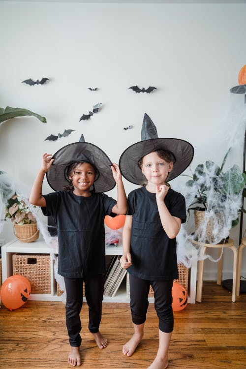 Two girls smiling in witch costumes