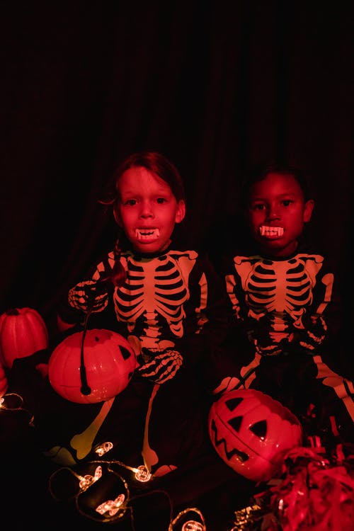 Two kids in Halloweencostumes seen in red light