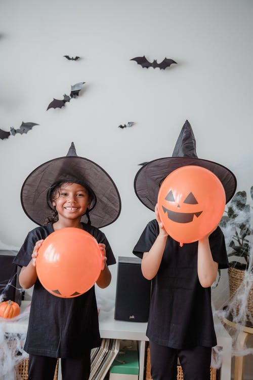 2 children dressed up for Halloween with orange balloons