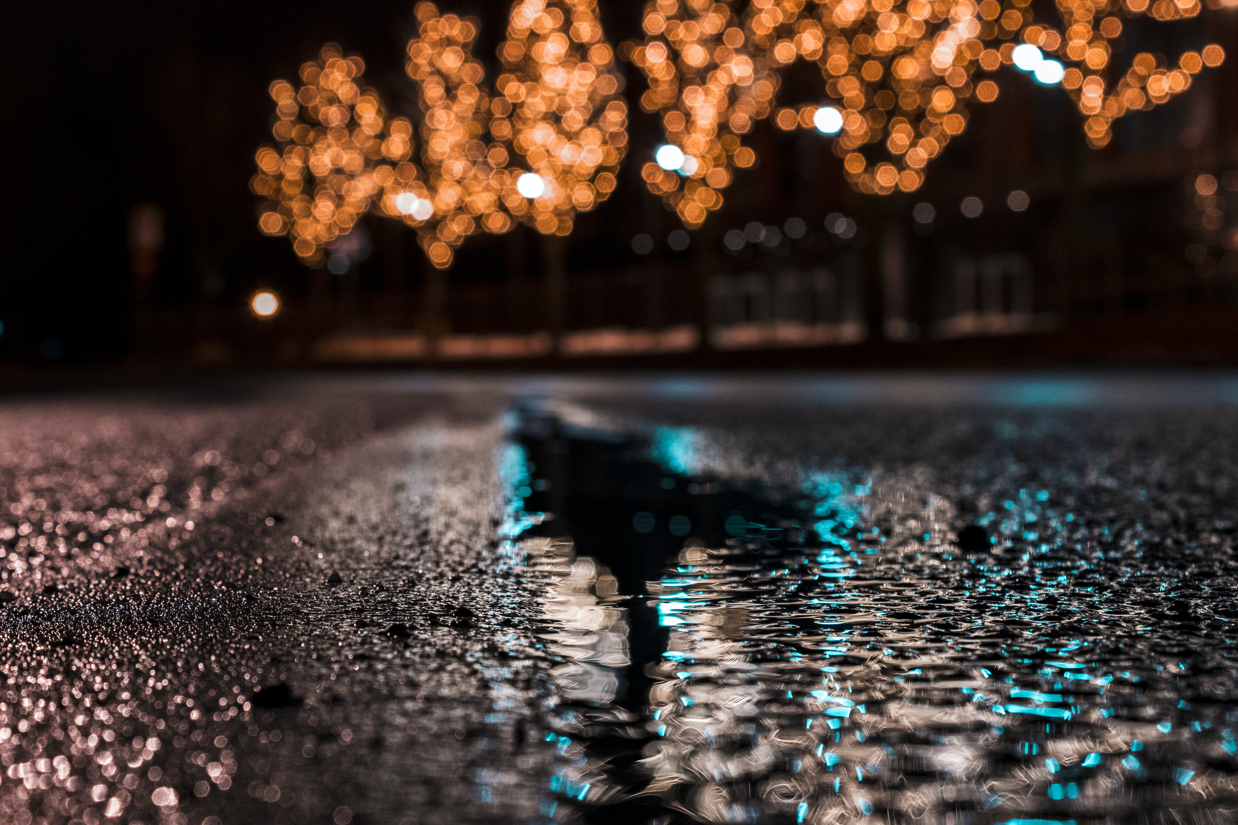 Selective Focus Photography of Asphalt Road With Water Droplets Near City Lights during Nighttime