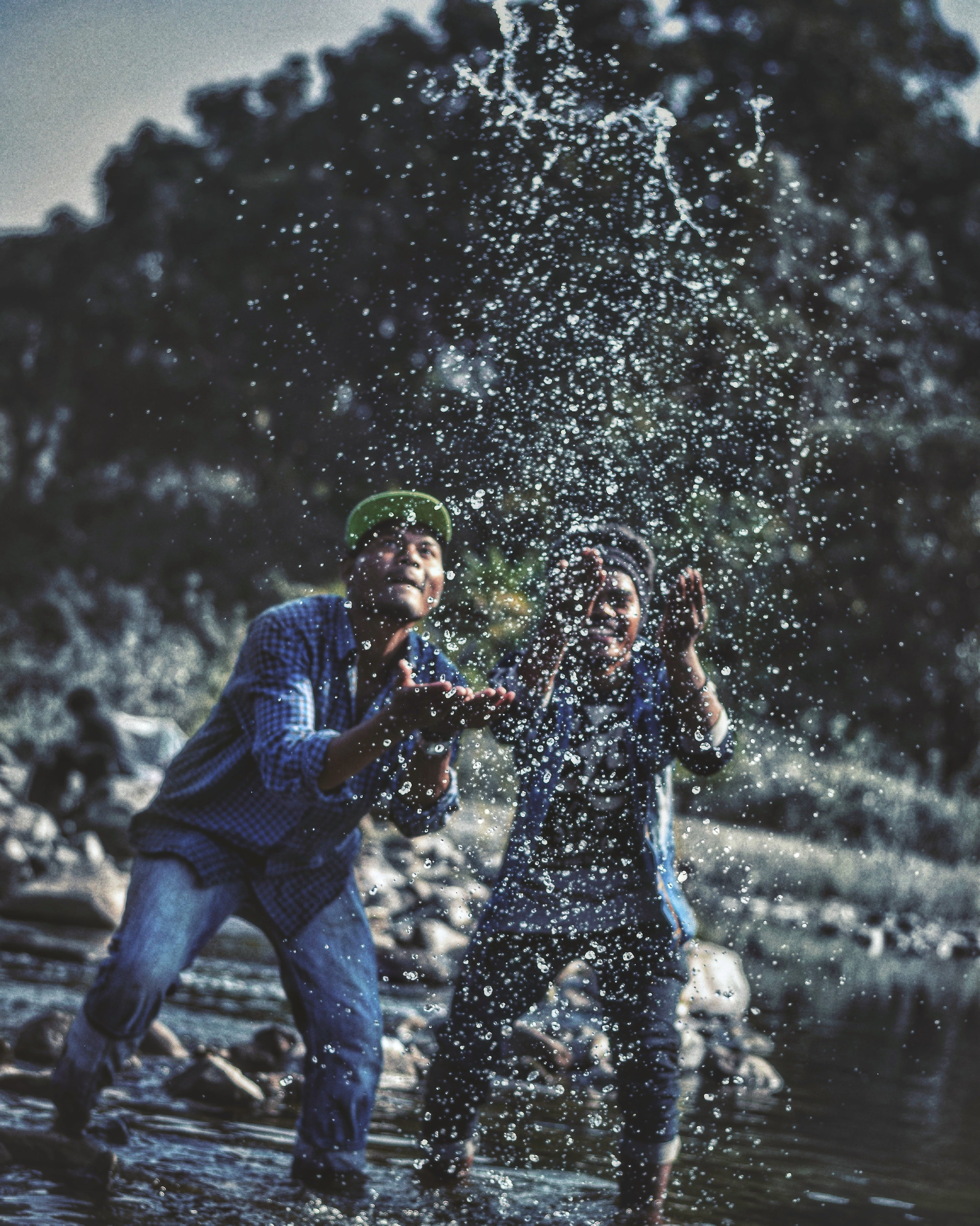 Two Men Playing With Water in Lake