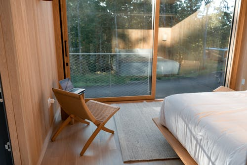 Brown Wooden Chair Beside White Bed