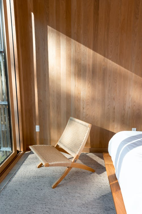 White and Brown Armchair Beside Brown Wooden Wall