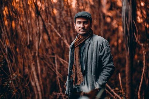 Man in Black Jacket Standing Near Brown Trees