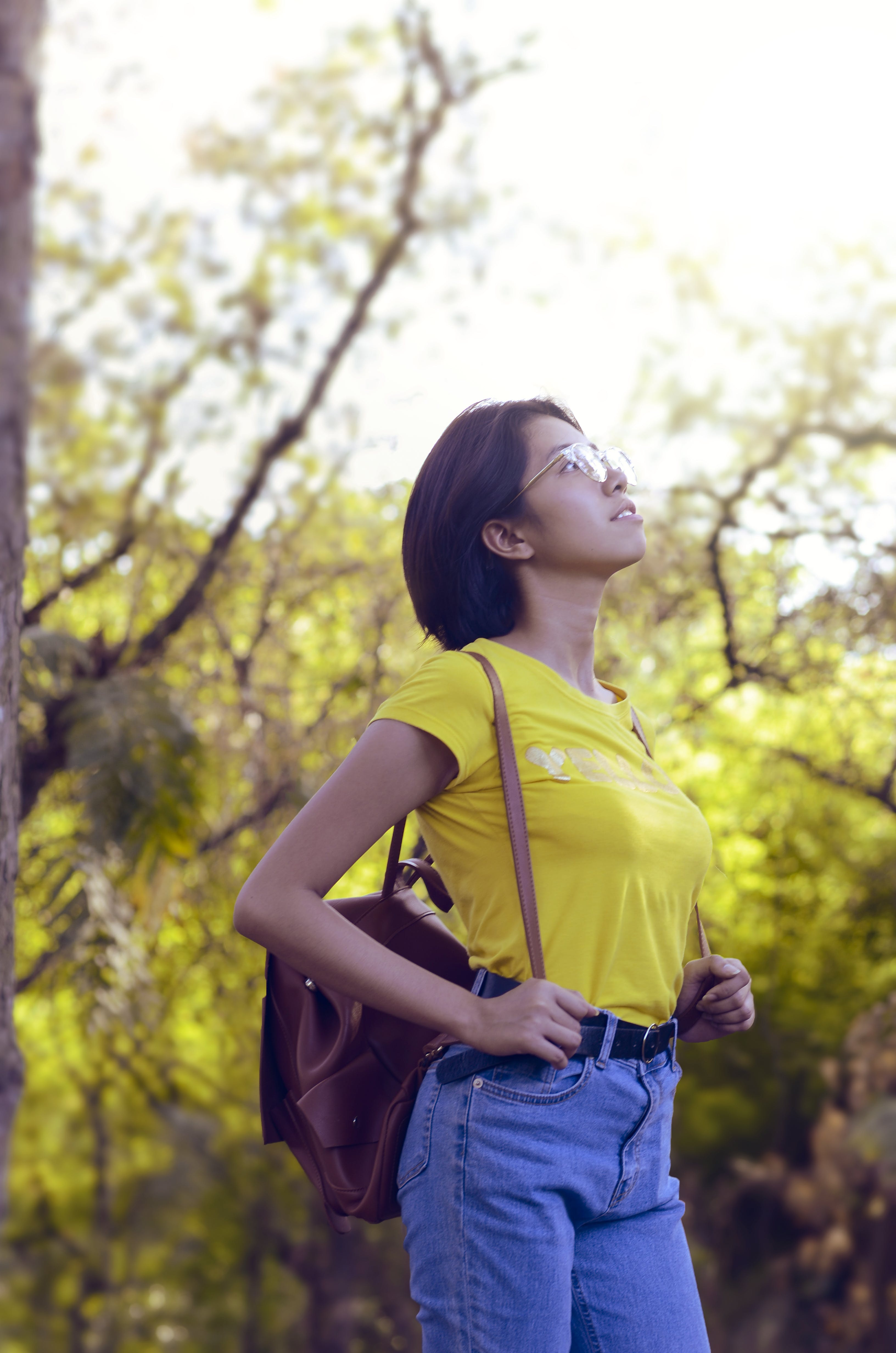 Woman Wearing Yellow Shirt and Looking Up Surrounded by Trees