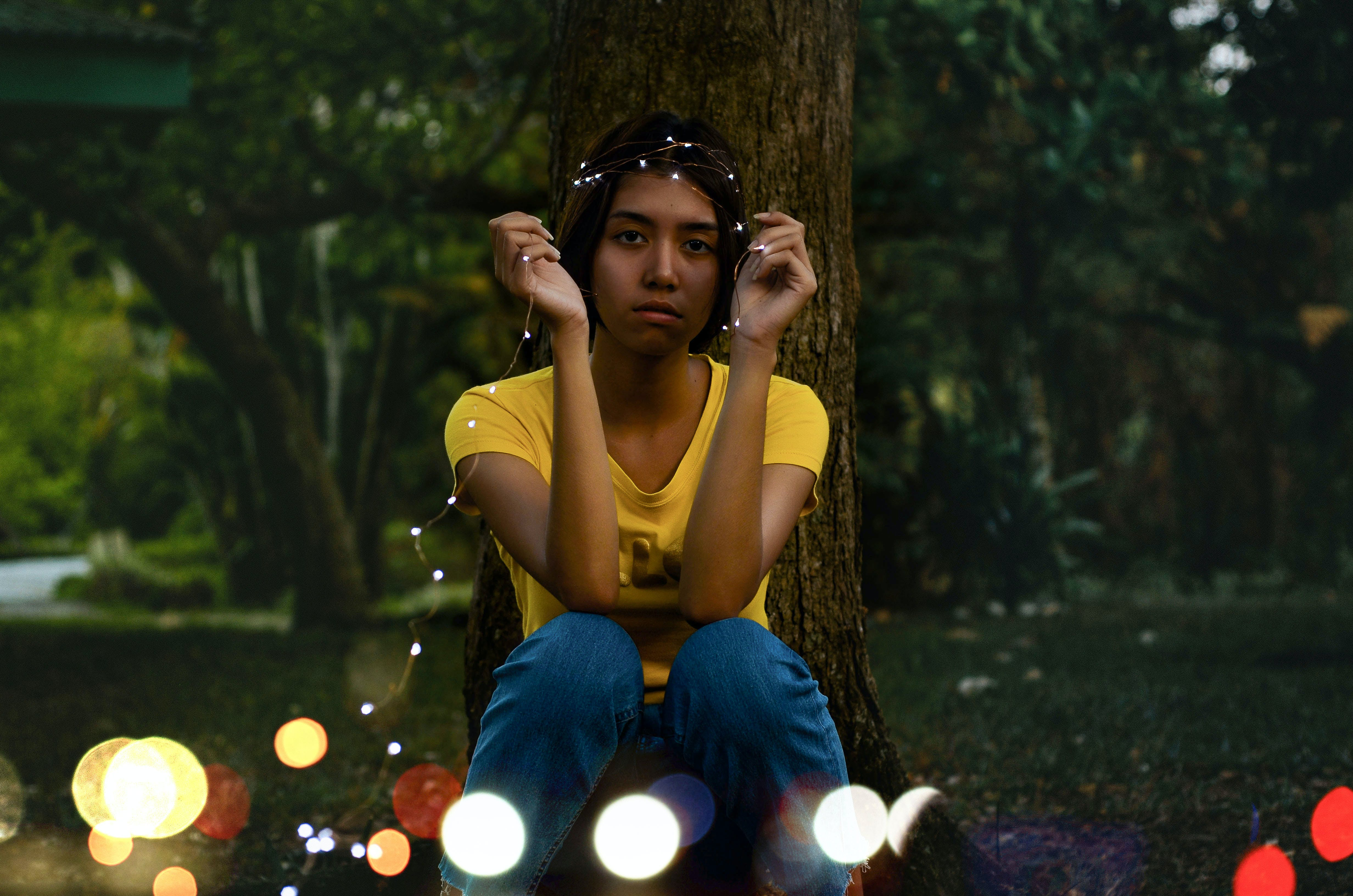 Girl in Yellow Top Sitting Beside Tree