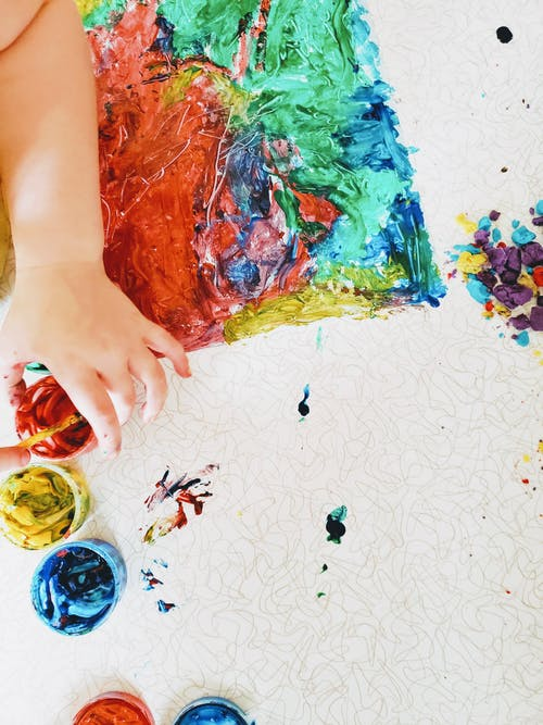 Person Holding Blue Red and Yellow Abstract Painting