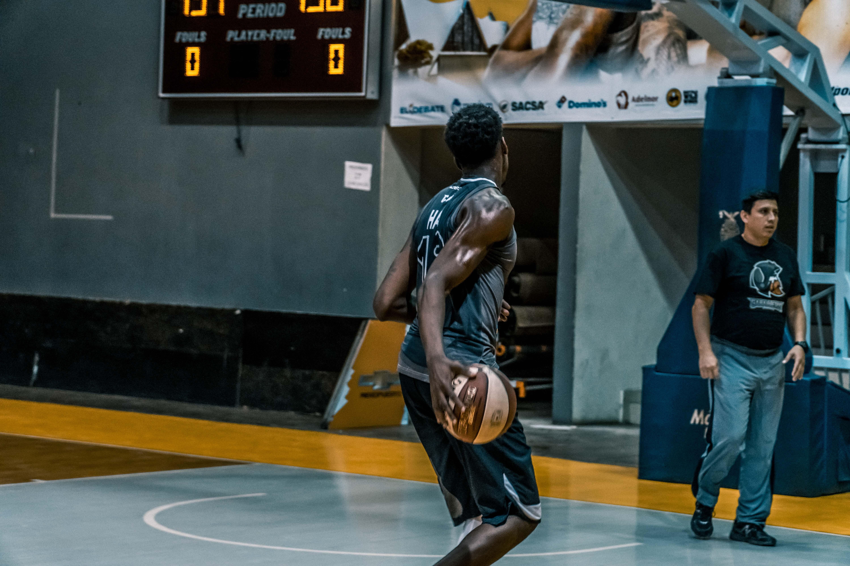 Man Holding Basketball on Blue Floor