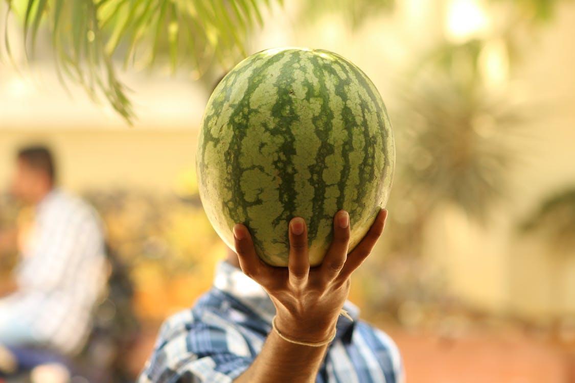 Selective Focus Photo of Man Raising the Watermelon