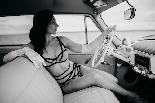 Woman in bikini sitting in car drivers seat