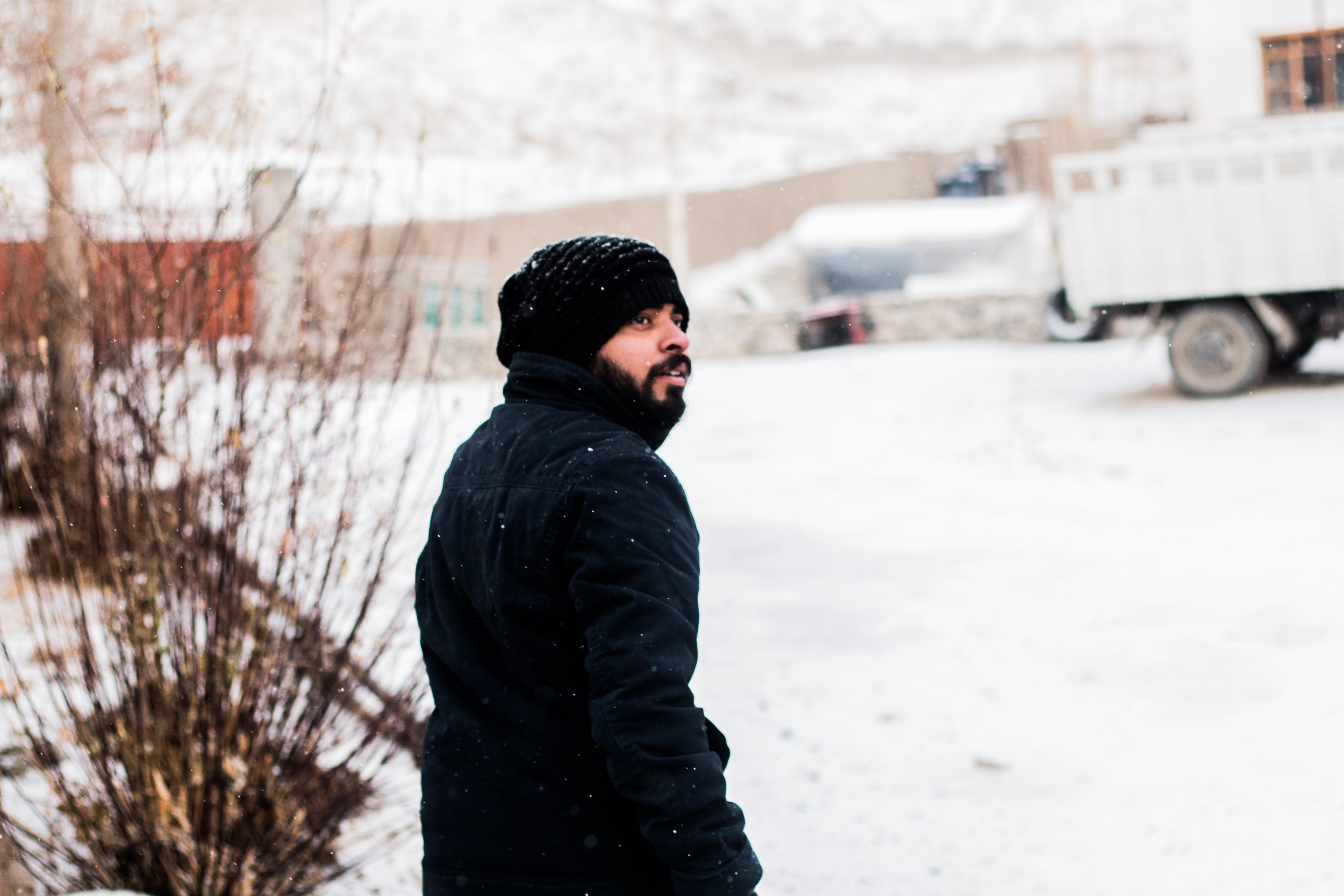 Photo of a Man Wearing Coat During Snow