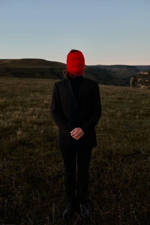 Man standing on the hill and having his head tied with a red crewel