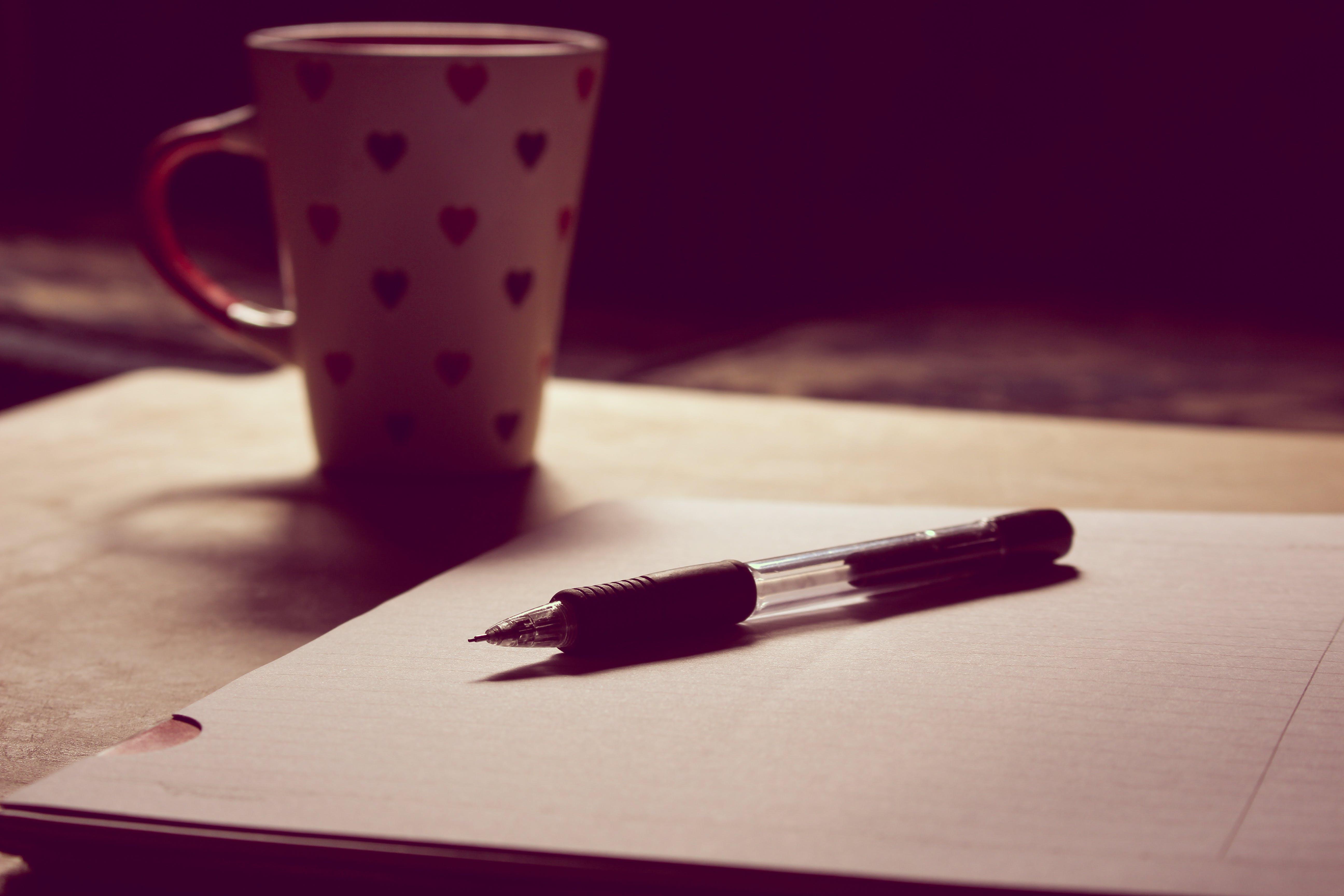 Black Pen on White Printed Paper Near White Ceramic Mug