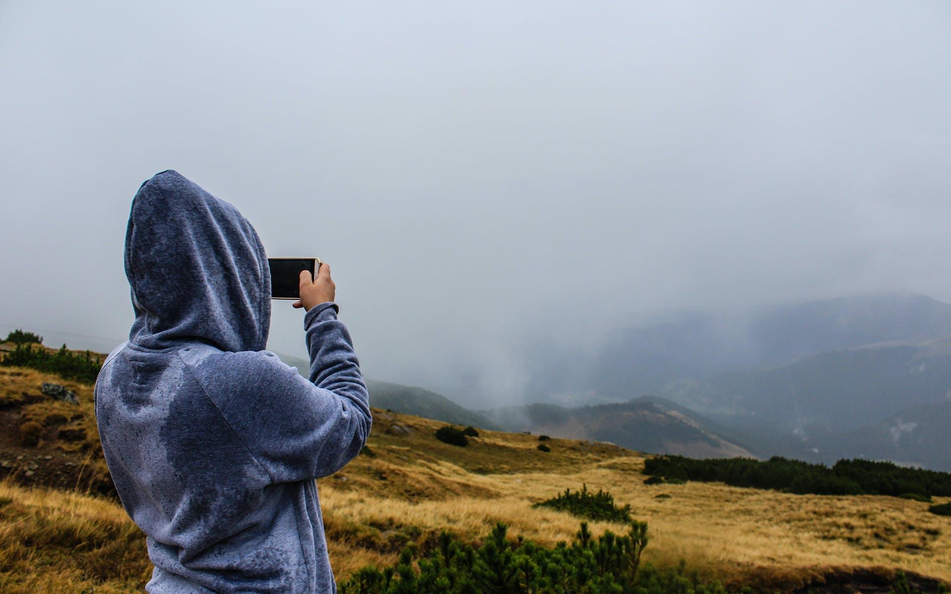 Person Taking Photo of Mountain