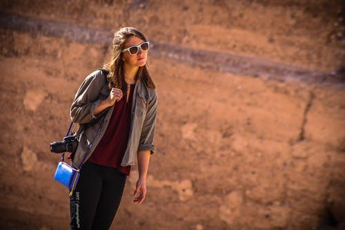 Woman Wearing Brown Jacket With Blue Leather Crossbody Bag
