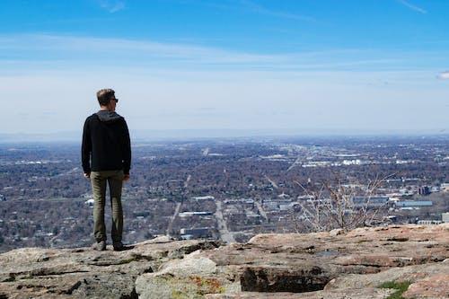 Man Wearing Black Jacket Standing on Rock Monolith