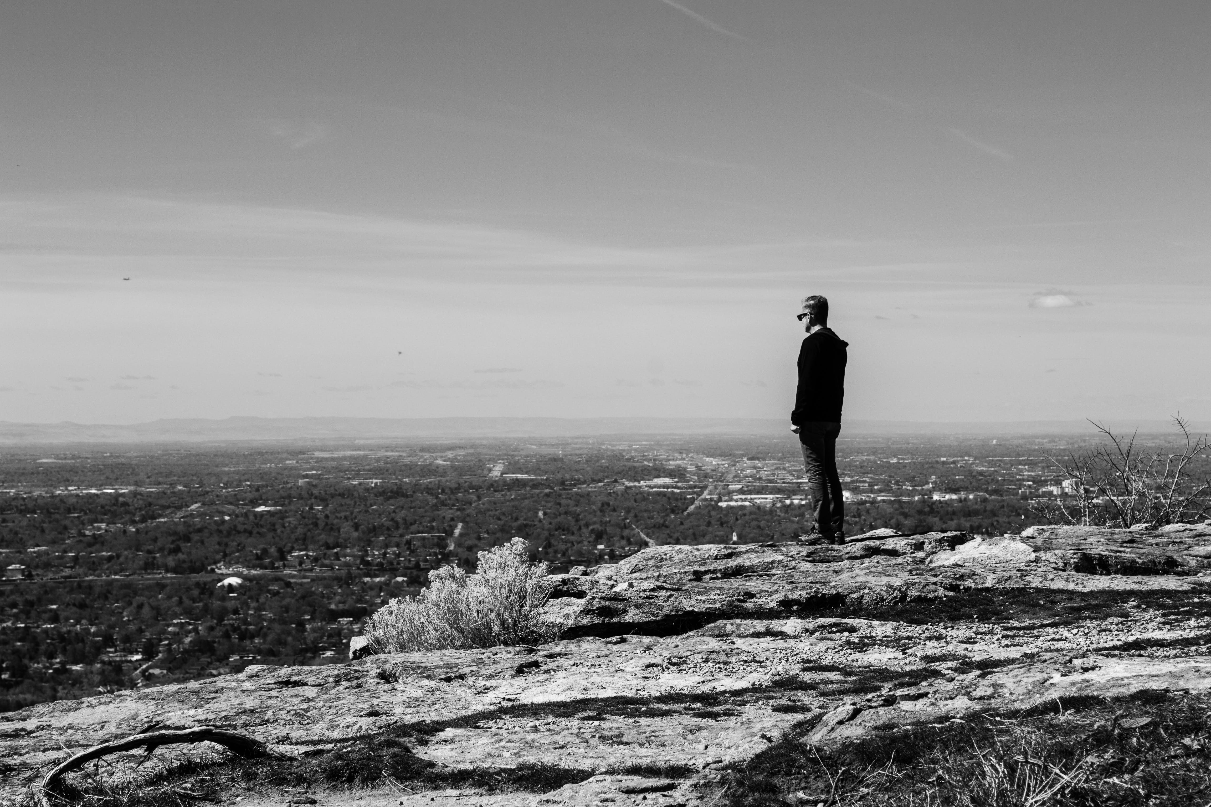 Greyscale Photography of Man Standing on Cliff in Front of Building