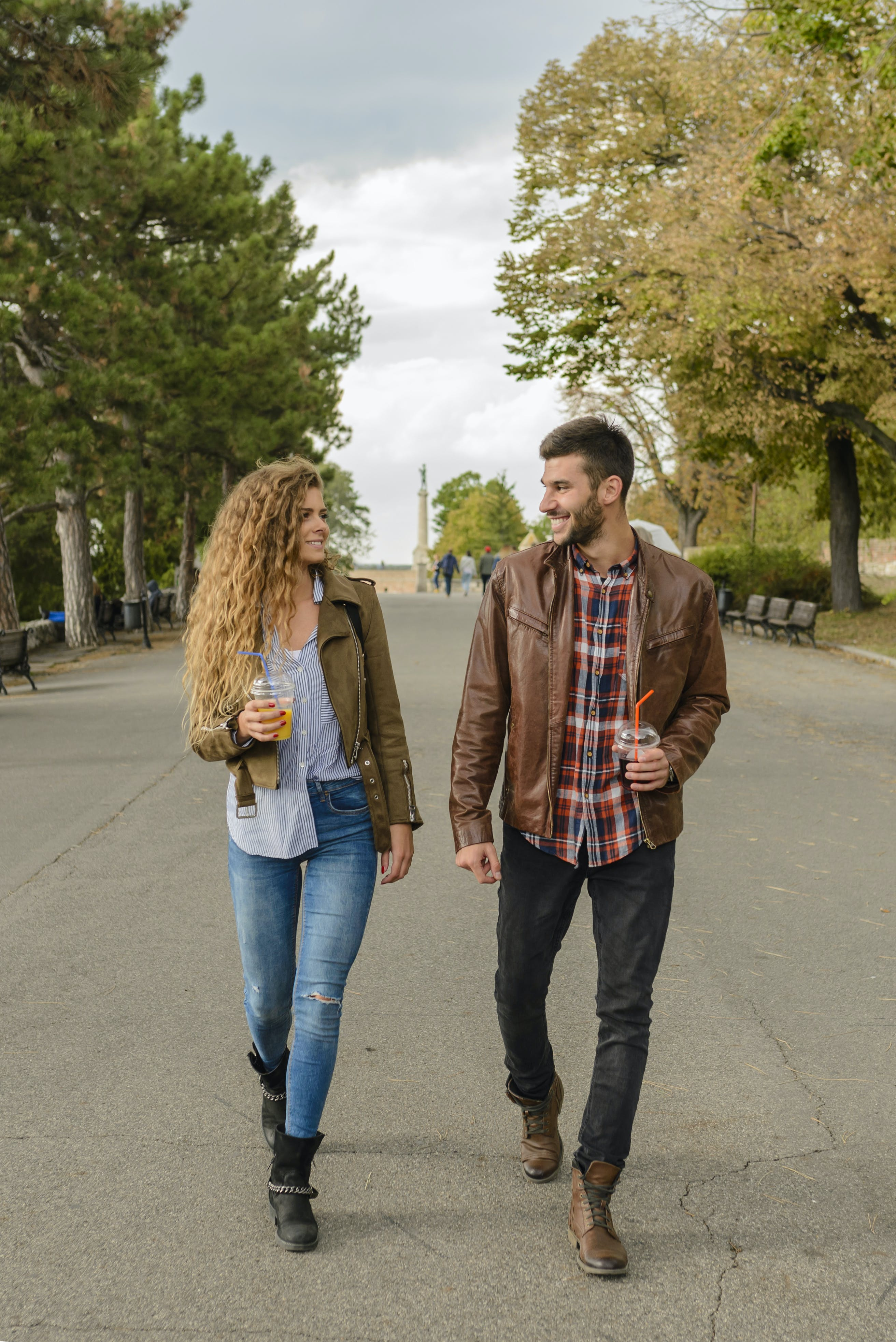 Man and Woman Wearing Brown Coats Walking on Pavement