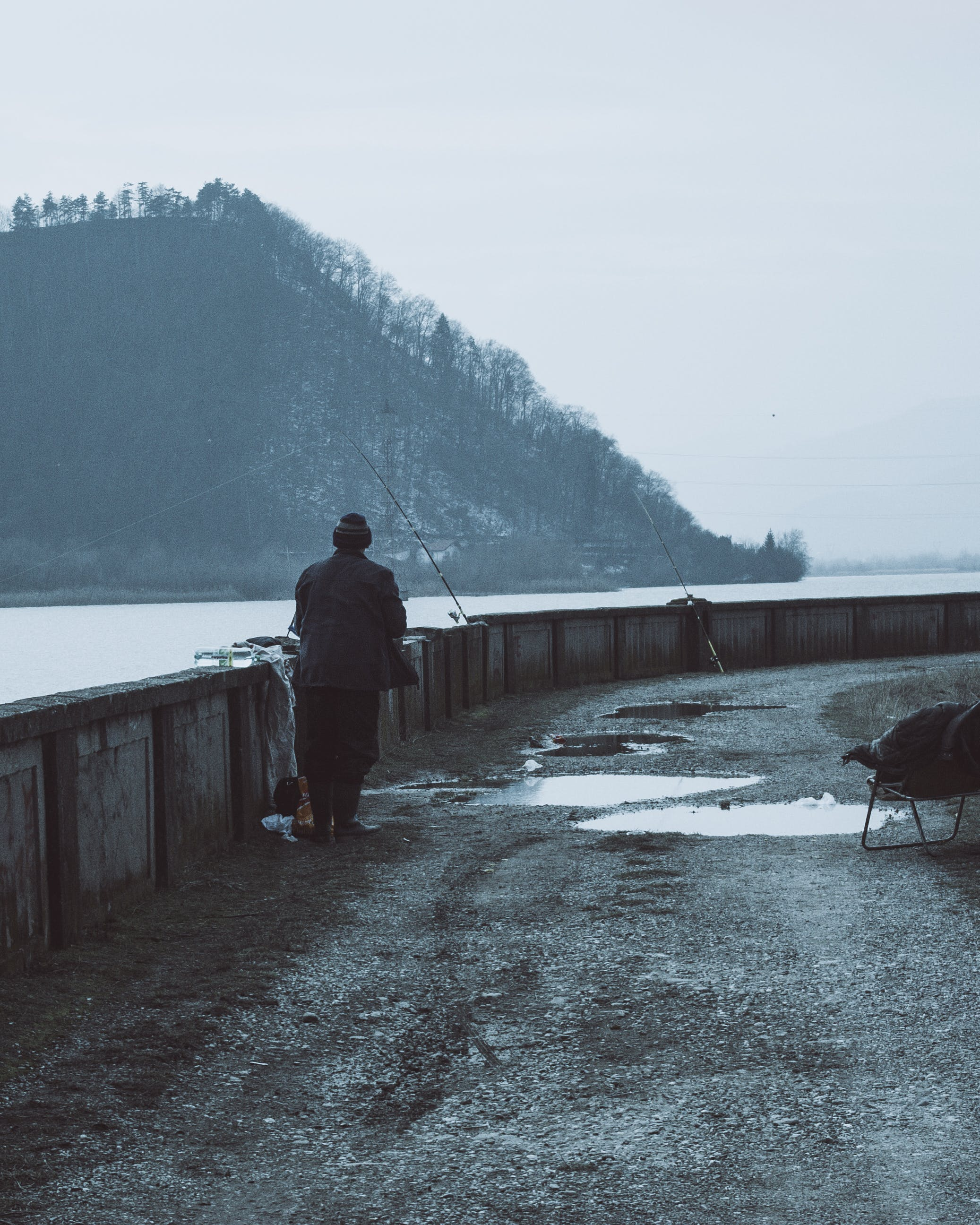Man Wearing Brown Coat Near a Body of Water With Fishing Rods at Daytime
