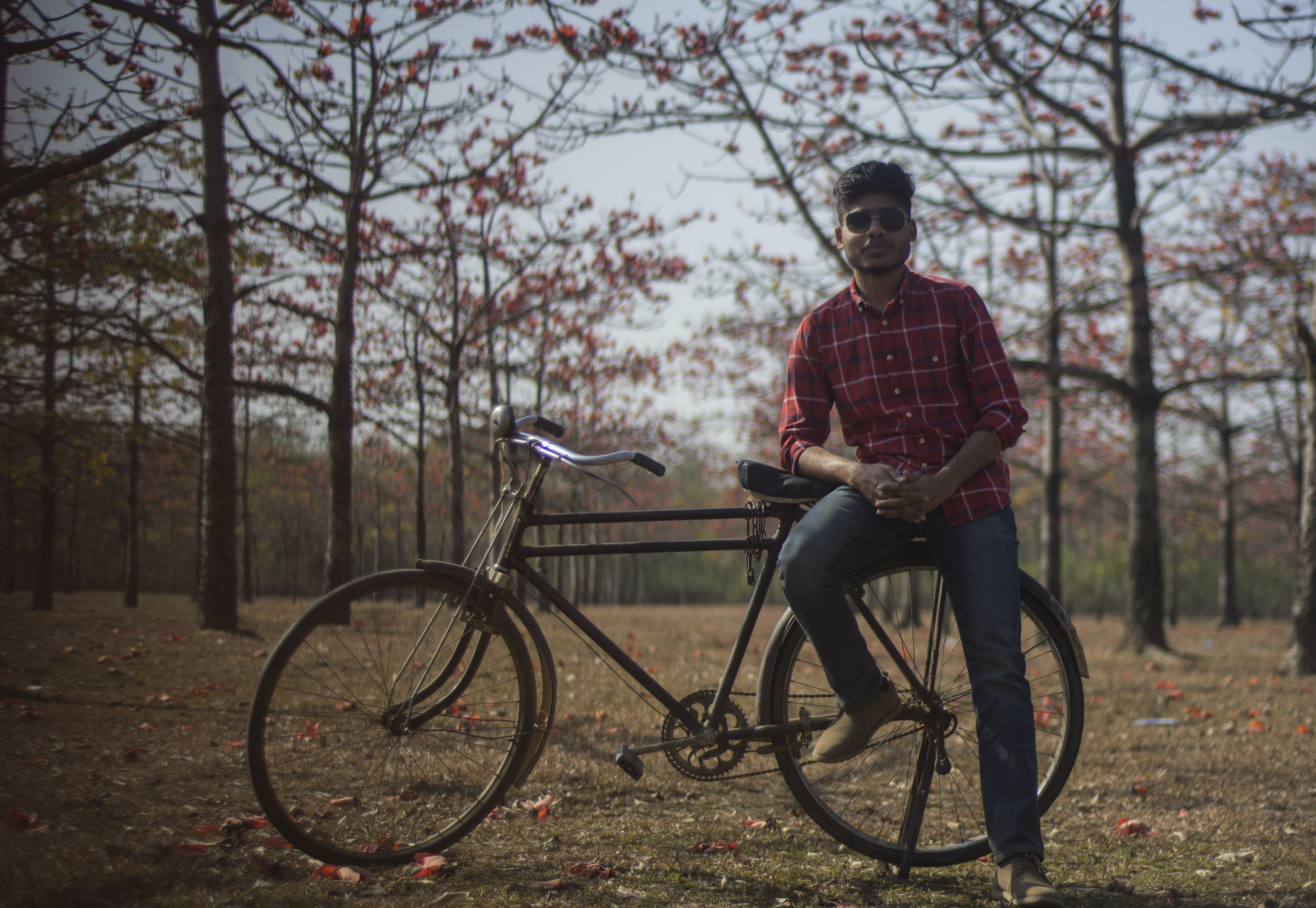 Man Wearing Red Dress Shirt and Blue Jeans Sitting on Black Bicycle