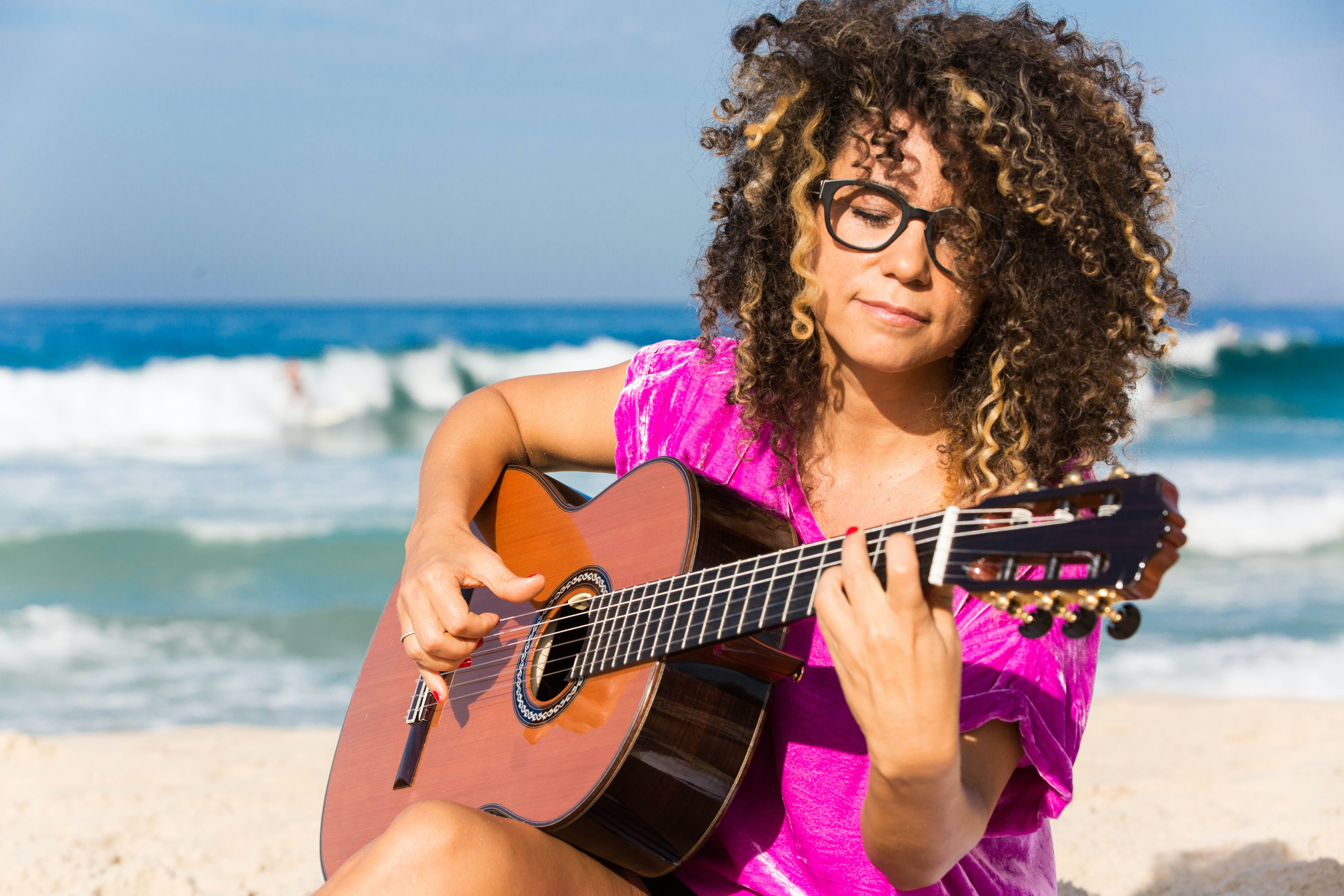 Woman Wearing Purple Shirt Playing Brown Classical Guitar While Sitting Near Shoreline With Water Splashing Background in Daytime