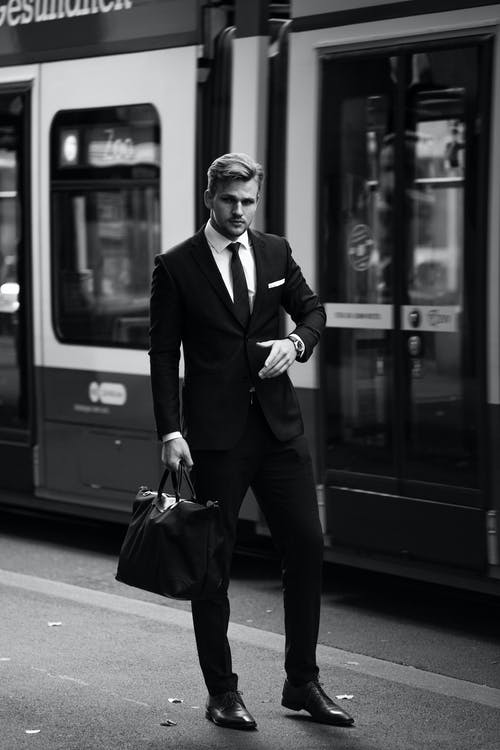 Full-suited man standing on rail station