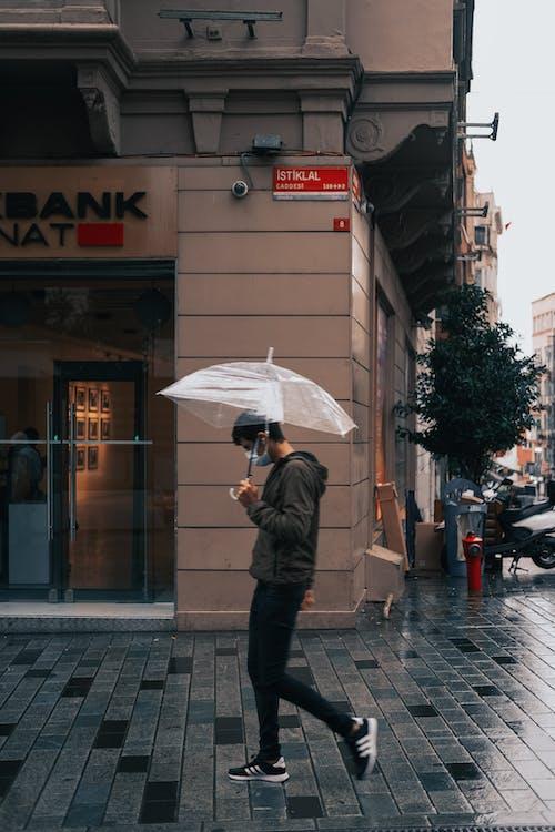 Man in Black Jacket Holding Umbrella Walking on Sidewalk