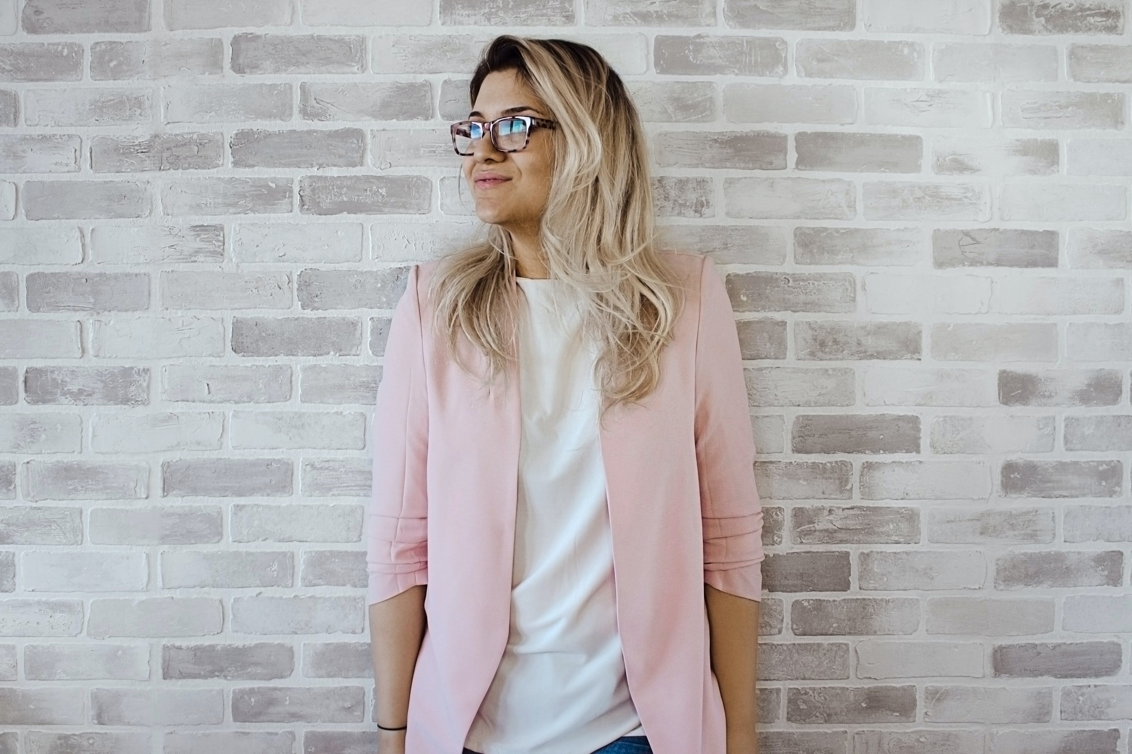 Woman in Pink Cardigan and White Shirt Leaning on the Wall