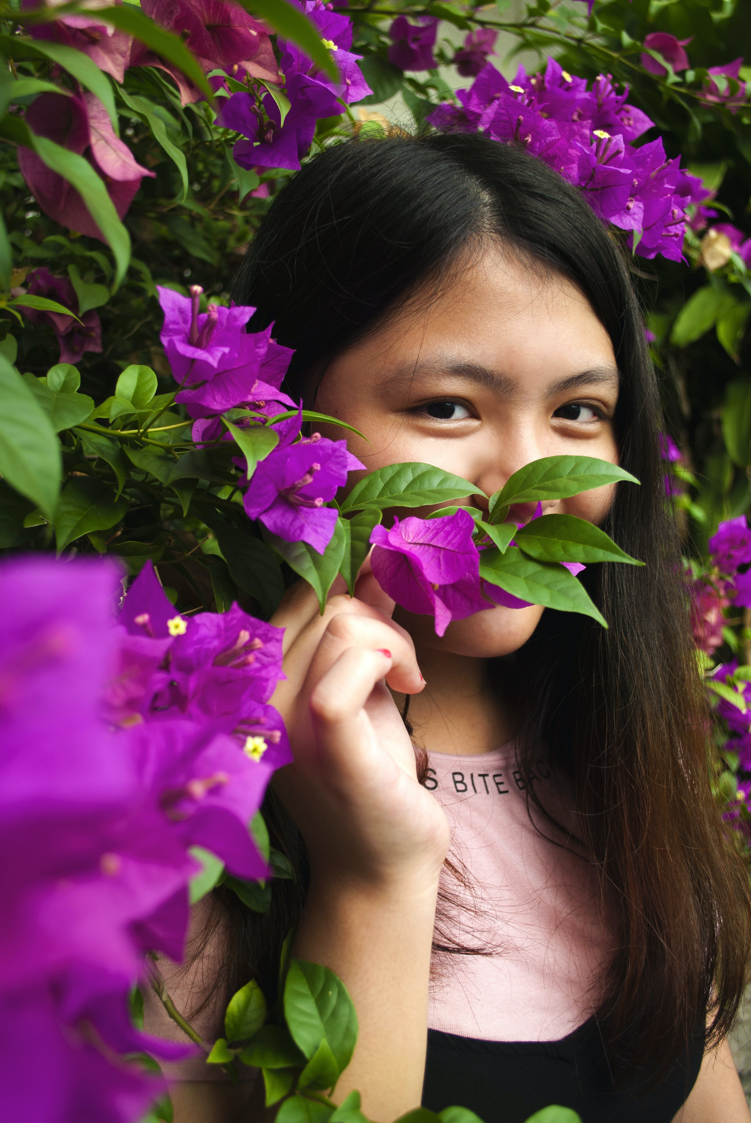 Woman Wearing Pink and Black Shirt Near Purple Petaled Flowers at Daytime