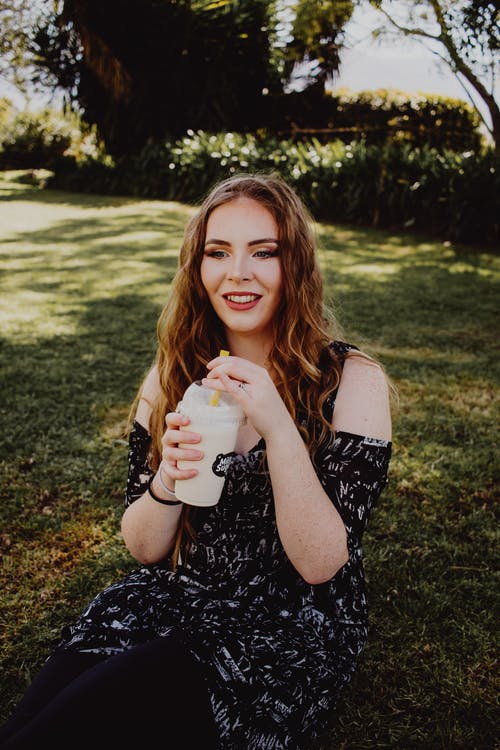 Pretty Woman Sitting on Grass Holding a Milk Tea