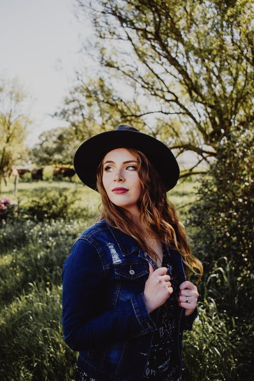 Woman in Denim Jacket and Black Hat Standing on Tall Grass