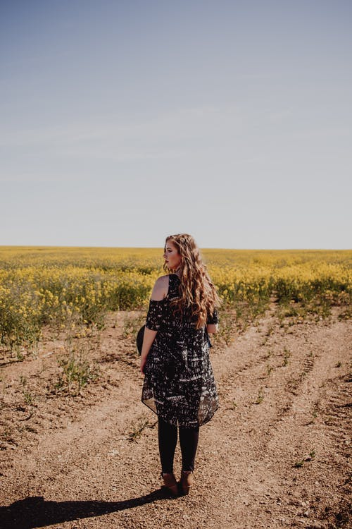 Woman in Black and White Floral Dress Standing on Brown Dirt Road