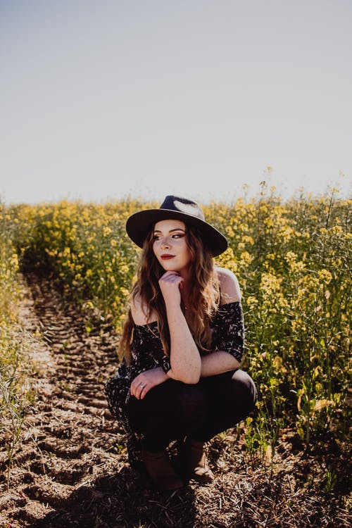 Woman in Black and White Floral Dress Wearing Black Hat Sitting on Ground Surrounded by Yellow