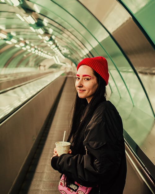 Woman in Black Coat and Red Knit Cap Holding White Disposable Cup