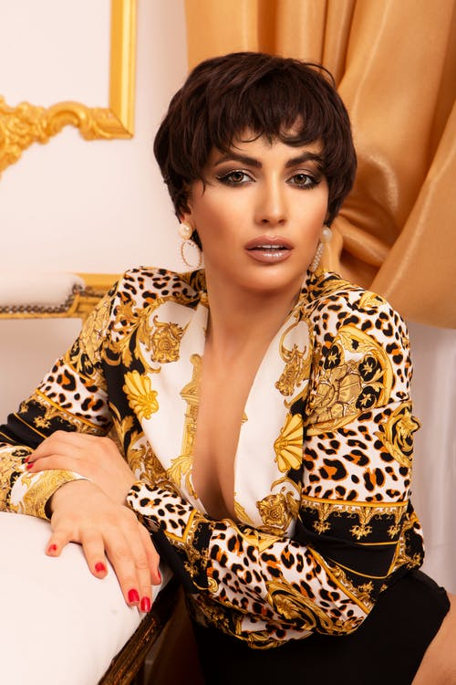 Woman Wearing a Animal Print Blouse Sitting Beside the Bed