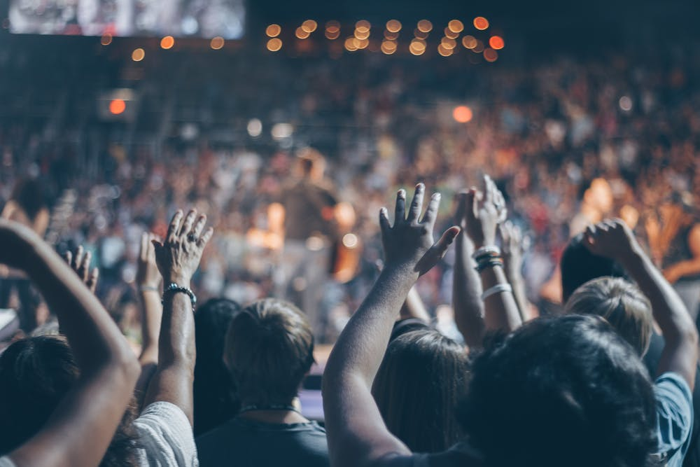 Group of people raise their hands on a stadium. | Photo: Pexels