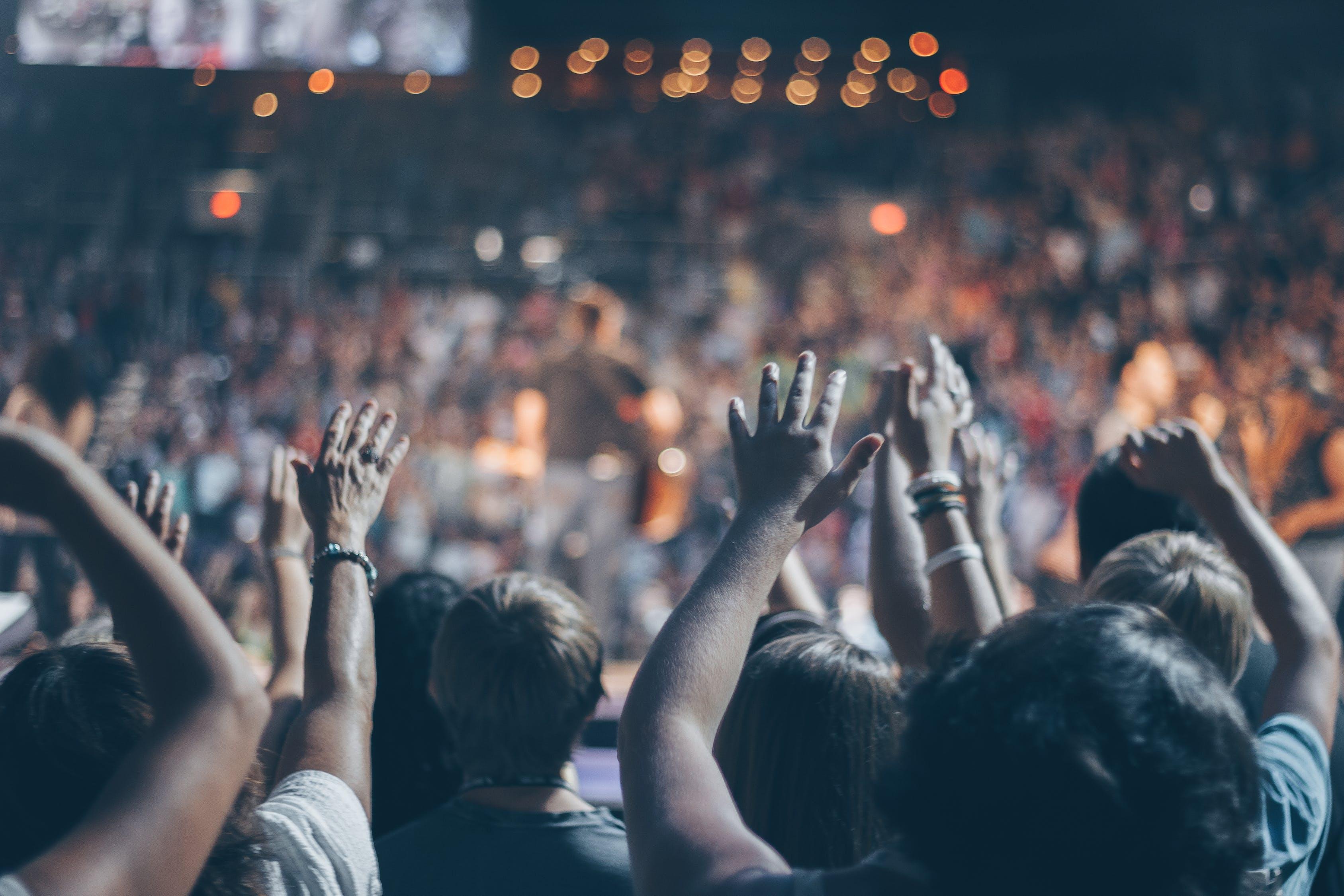 Grupo De Pessoas Levanta As Mãos No Estádio