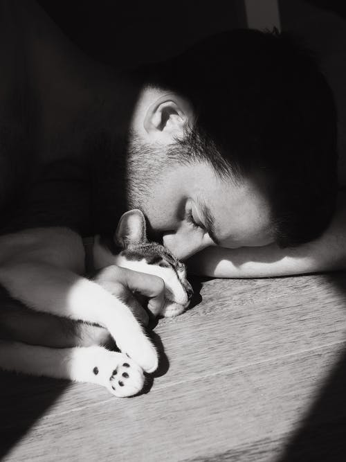 Grayscale Photo of Man Lying with a Cat