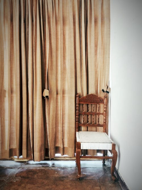 Brown And White Wooden Chair Beside A Brown Window Curtain