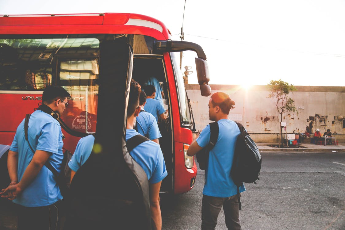 Group of Men Wearing Blue Shirts About to Enter Red Bus