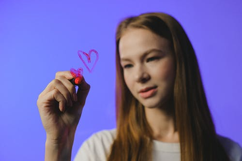 Girl drawing heart on glass against blue background