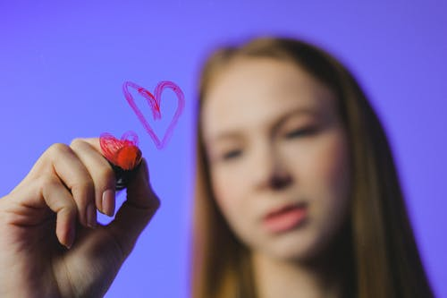 Teenage girl drawing heart symbol on glass